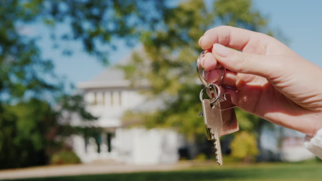 The hand holds the key to the house. Rent and purchase of housing concept