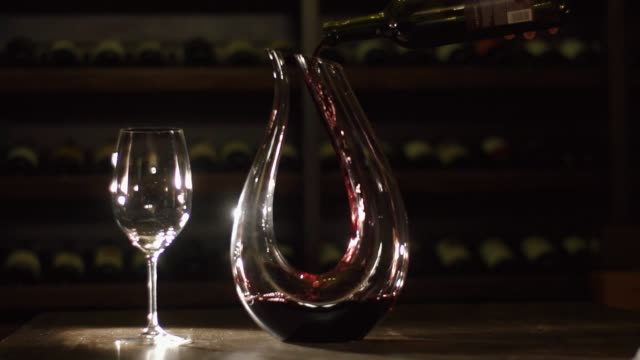 The hand is pouring the red wine in alsmost full decanter standing near the wine glass on the table. video