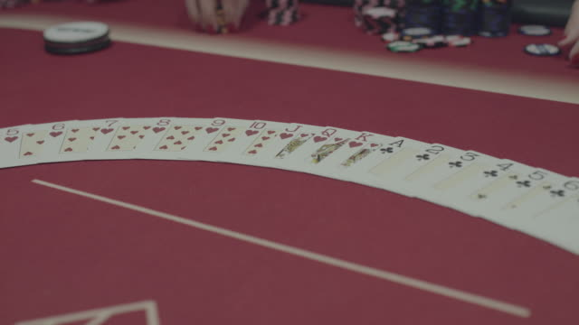 The hand laying out the pocker cards on table during game video