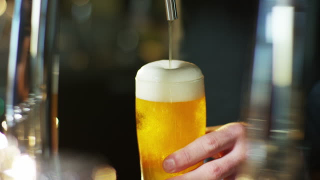 the hand of a master brewer plug a light beer foam and perfectly natural. - birra video stock e b–roll