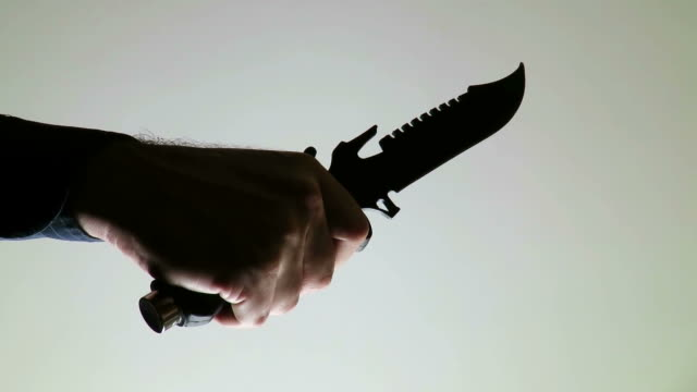 The hand of a white adult man in the shadow , holding with a strong grip a hunting knife , against a grey dark background video