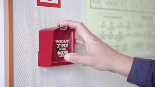 vídeos de stock e filmes b-roll de the hand of man is pushing fire alarm on the wall. clip. hand of man pushing fire alarm switch on the white wall as background for emergency case at the new factory building - puxar