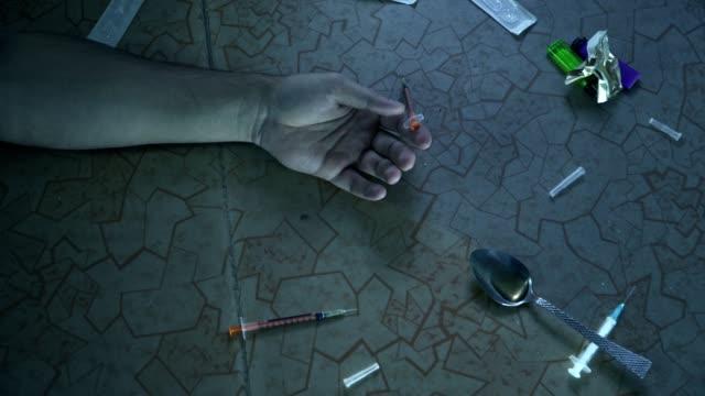 stockvideo's en b-roll-footage met de hand van de verslaafde valt op de vloer na het nemen van de dosis. dood van een drugsverslaafde. - amfetamine