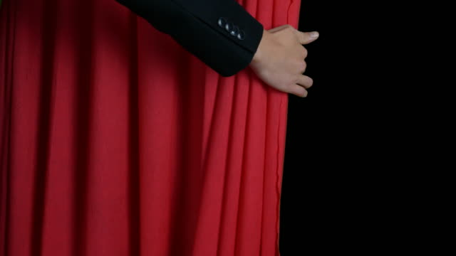 The hand opens the curtain