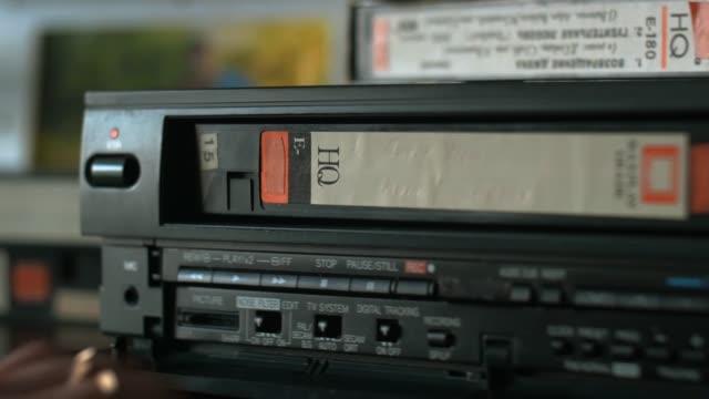 手、ビデオテープを受け取り、ビデオ プレーヤーに挿入し、再生をプッシュ - アナログレコード点の映像素材/bロール