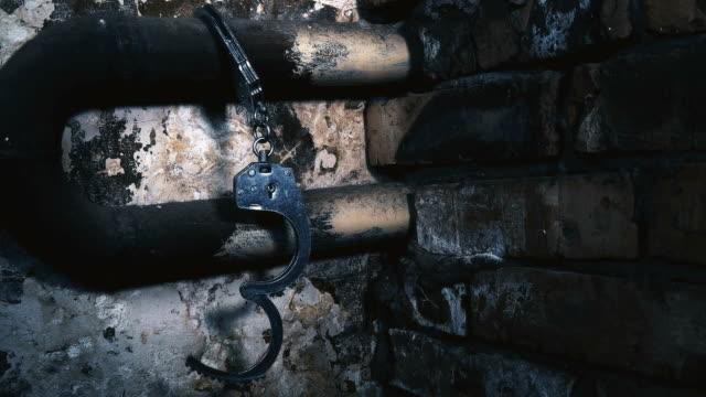 handfängsel fastkedjad vid en pipa i en gammal byggnad - kriminell bildbanksvideor och videomaterial från bakom kulisserna
