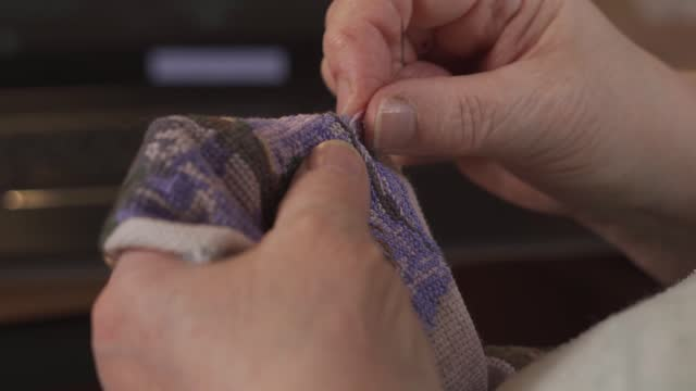 vídeos de stock, filmes e b-roll de as mãos de uma idosa bordam uma cruz - feito em casa