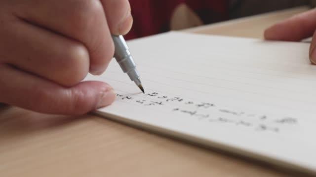 vídeos de stock e filmes b-roll de the hands of the senior woman writing a letter. - mensagem