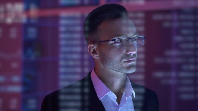 vídeos y material grabado en eventos de stock de el empresario guapo en la oficina de la noche en el fondo del holograma - bien parecido