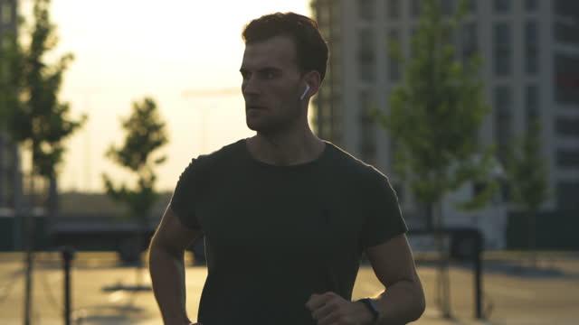l'uomo bello sta facendo jogging al mattino. rallentatore - auricolari wireless video stock e b–roll