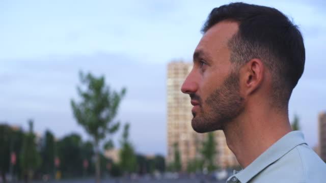 vídeos de stock, filmes e b-roll de o homem bonito tira a máscara ao ar livre - relevo
