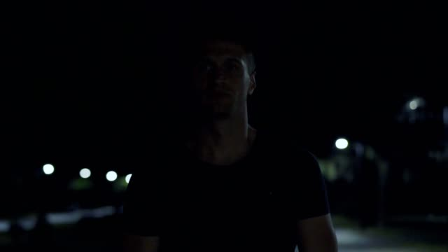 The handsome man walking in the dark street. slow motion