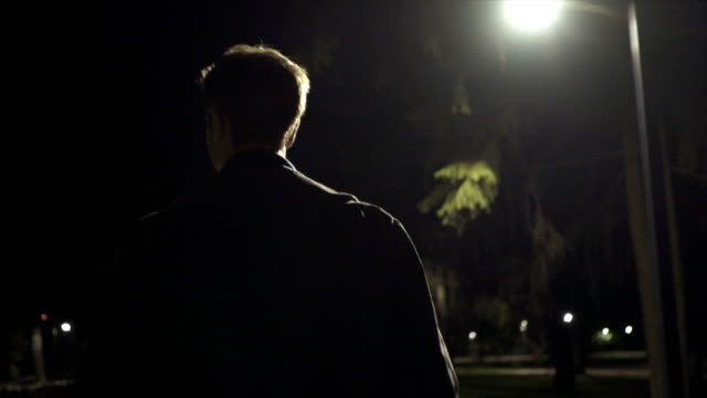 the handsome man walking outdoor. evening night time, slow motion - solo un uomo video stock e b–roll