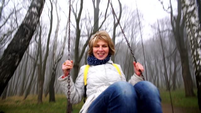 The happy beautiful active attractive 50-years-old mature woman swinging on the swings in the park video