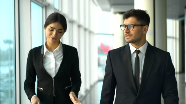 The happy businessman and a businesswoman walking in the office. slow motion