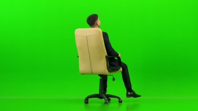 녹색 배경에 사무실의 자를 켜고 행복 한 사업가 - 앉음 스톡 비디오 및 b-롤 화면