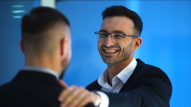 the happy businessmen pat shoulder on the blue background. slow motion - rispetto video stock e b–roll