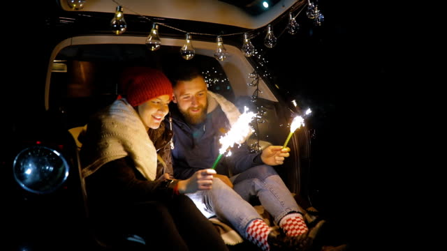 The happy couple hold a firework sticks. evening night time video