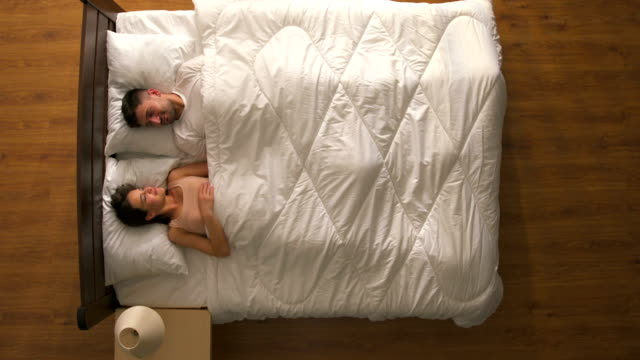 The happy couple wake up in the bed. view from above