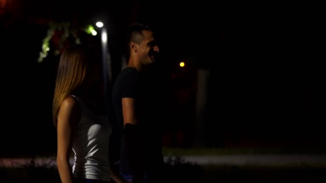 The happy couple walking in the park. evening night time. slow motion
