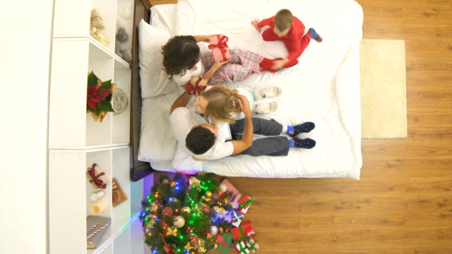 The happy family opening gifts on the bed near a christmas tree. view from above