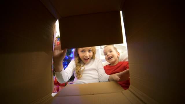 de glada barn öppna rutan nära julgranen - christmas presents bildbanksvideor och videomaterial från bakom kulisserna