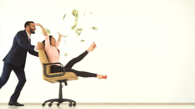 vidéos et rushes de l'heureux homme et une femme jouant avec une chaise et une d'argent. slow motion - lancer