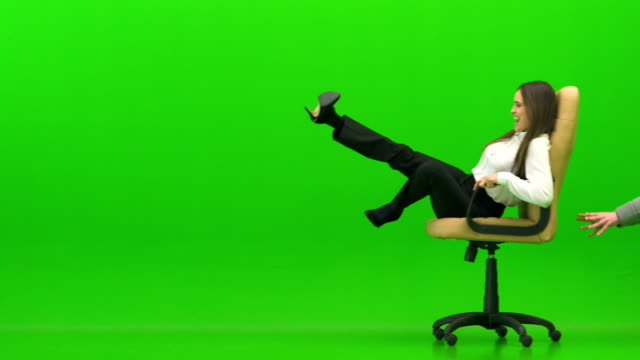 The happy woman playing on the office chair on the green background The happy woman playing on the office chair on the green background chair stock videos & royalty-free footage