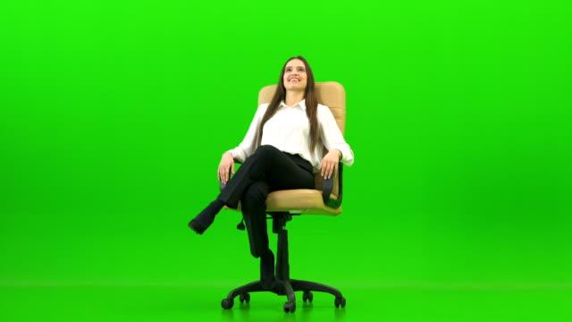 녹색 배경에 사무실의 자를 켜고 행복 한 여자 - 앉음 스톡 비디오 및 b-롤 화면