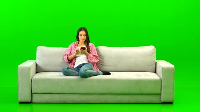 den lyckliga kvinnan med en telefon sitter på soffan på den gröna bakgrunden - sitta bildbanksvideor och videomaterial från bakom kulisserna