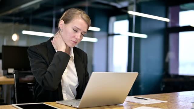 vídeos de stock, filmes e b-roll de a mulher de negócios nova trabalhadora que tem a dor da garganta no escritório - ortopedia