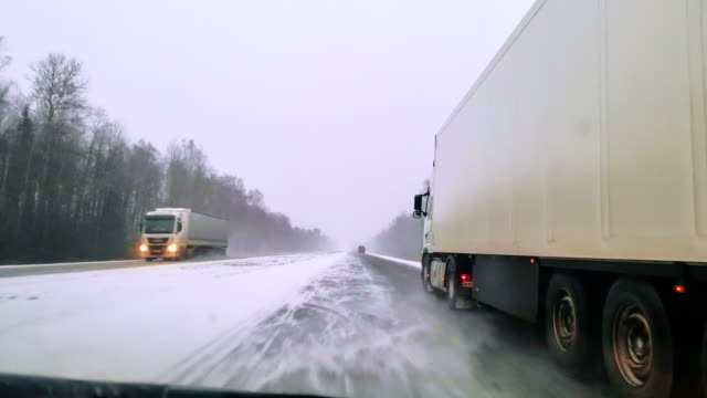 the heavy cargo trucks driving on the highway in the terrible snowy windy weather. the view through the windshield - driver point of view. mobile video. - лёд стоковые видео и кадры b-roll
