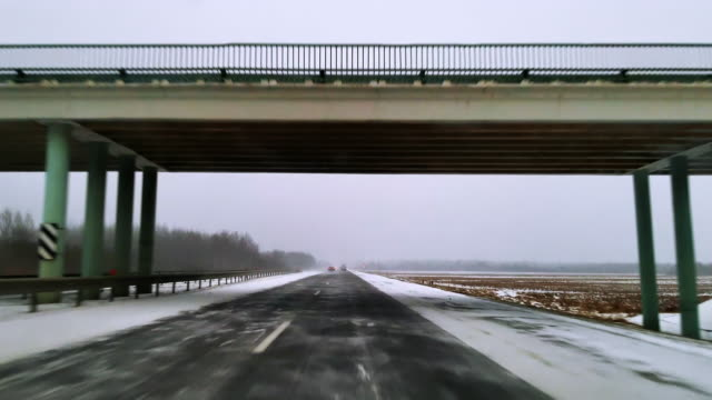 the heavy cargo trucks driving on the highway in the terrible snowy windy weather. the view through the windshield - driver point of view. mobile video. - sotto video stock e b–roll