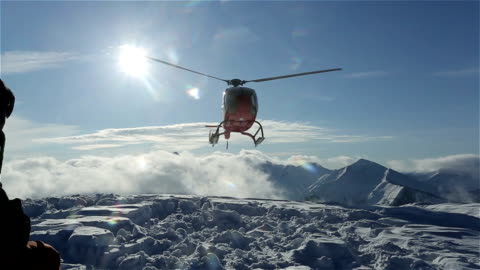 The helicopter left skiers on the slope of the mountain and flew raising a cloud of snow The helicopter left skiers on the slope of the mountain and flew raising a cloud of snow. Lake Baikal, Siberia. helicopter stock videos & royalty-free footage