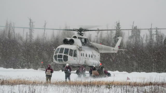The helicopter takes off in a snowstorm. The helicopter brought cargo to the oil field. Then took off and disappeared in a snowstorm siberia stock videos & royalty-free footage