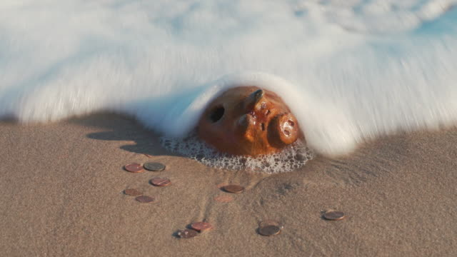 The hidden treasure was uncovered by the ocean. The vintage antique piggy bank and coins in the surf on a beach. Waves come and gone, leaving the coin bank and money on the sand.