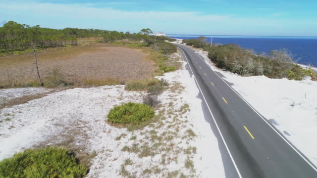The highway along white sand dunes and pine forest on the Atlantic coast at Alligator Point, Panacea, North Florida. Aerial drone video with the cinematic forward camera motion..