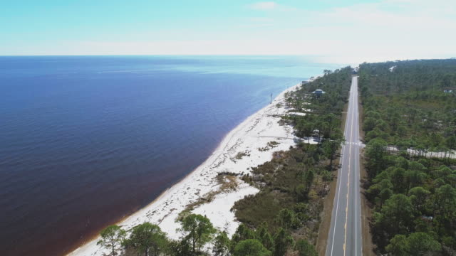 The highway along white sand dunes and pine forest on the Atlantic coast at Alligator Point, Panacea, North Florida. Aerial drone video with the cinematic descending and panning around camera motion..