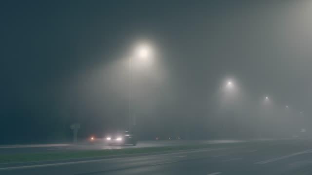 stockvideo's en b-roll-footage met de snelweg aan twee kanten laat bij nacht in mistig weer. het licht van de streetlights in de mist. passerende auto's in de avond trage snelheid - mist donker auto