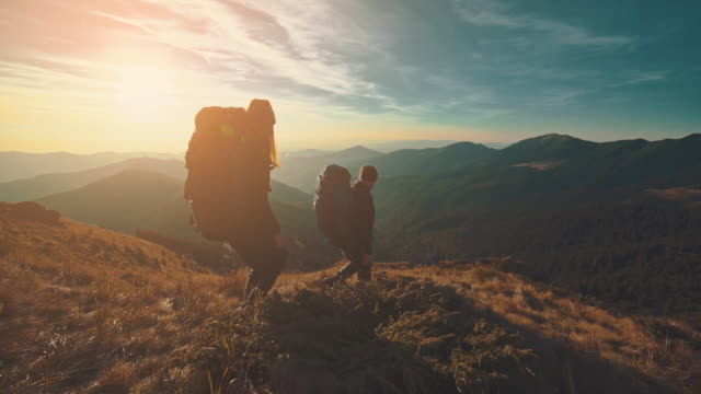 vídeos de stock e filmes b-roll de the hikers walking in the mountain on the sunrise background. slow motion - mochila saco
