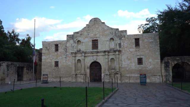 the historic alamo at dusk with texas flag flying at half mast panning video - san antonio texas stock videos & royalty-free footage