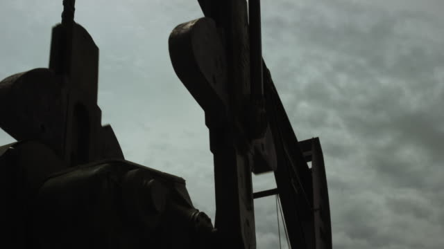 The Horsehead and Walking Beam of an Oil Pumpjack Bobs up and Down in Silhouette against an Overcast Sky as It Pumps Oil from under the Ground The Horsehead and Walking Beam of an Oil Pumpjack Bobs up and Down in Silhouette against an Overcast Sky as It Pumps Oil from under the Ground oil stock videos & royalty-free footage