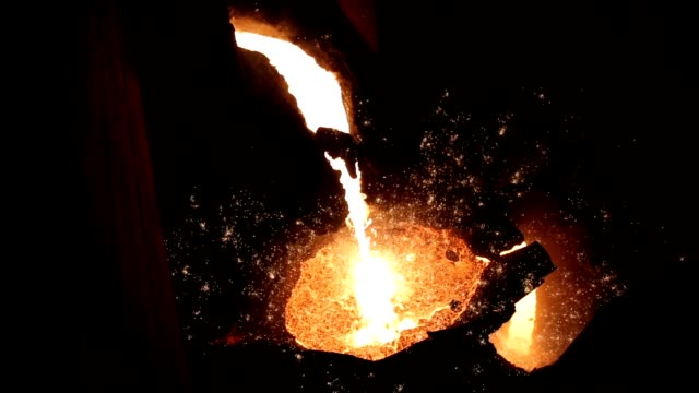the hot avalanche of cast iron flows like water. metallurgy. - industria metallurgica video stock e b–roll
