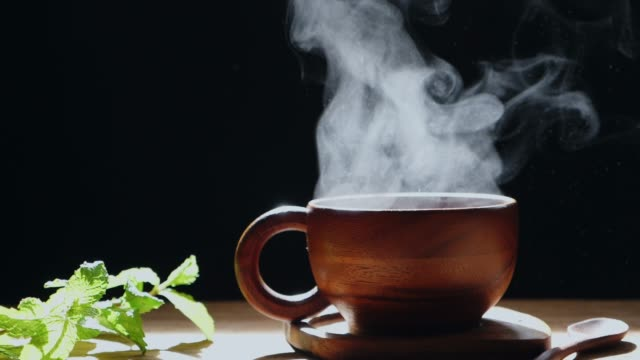 the hot tea in the wooden cup has white smoke. - tea cup stock videos & royalty-free footage