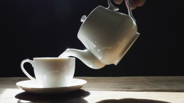 the hot water that is pouring from the glass jug into the white cup has white smoke and the black background. slow motion - teapot stock videos & royalty-free footage