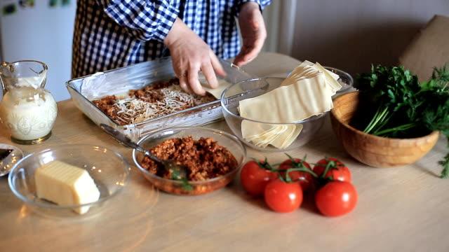 vidéos et rushes de la femme au foyer cuisine lasagne à la viande dans la cuisine. nourriture faite maison - recette