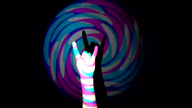 The human hand doing horns sign with his fingers on background of colorful tunnel flythrough loop