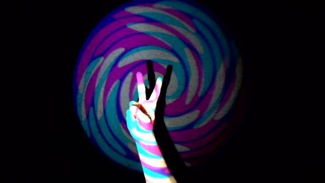 The human hand showing victory sign on background of colorful tunnel flythrough loop
