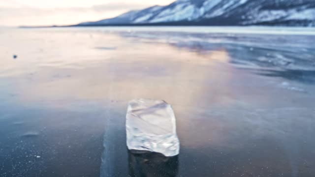 the ice floe rotates on the ice against the background of the amazing mountain landscape. slow motion. the camera moves behind the ice. ice is very beautifully spinning on ice with magical cracks. - ghiaccio galleggiante video stock e b–roll