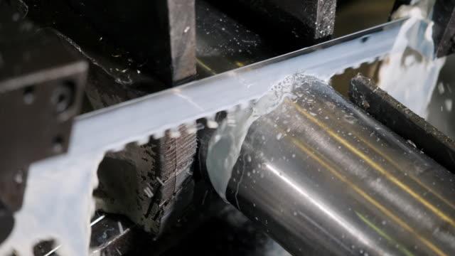 die industriesägemaschine, die die materialstange schneidet. das band sägen maschine schneiden rohmetallstäbe die mit der kühlmittelflüssigkeit. - bandsäge stock-videos und b-roll-filmmaterial